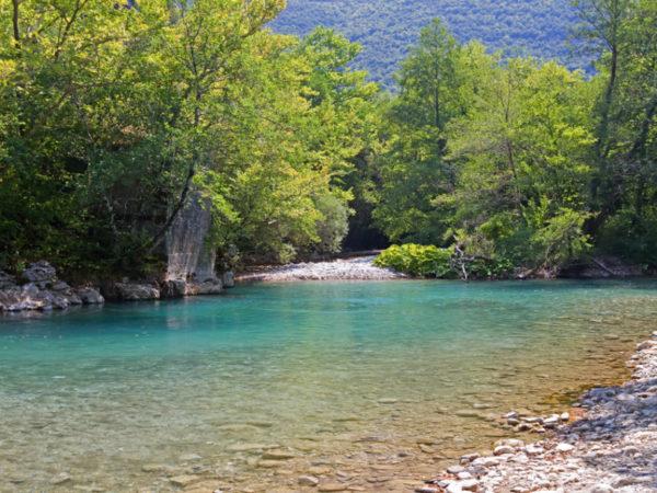 The blue waters of Voidomatis river that flows through Epirus region, Greece